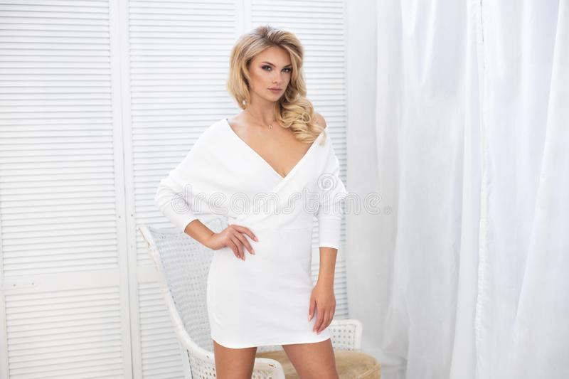 Attractive fashion model wears a white dress in studio and smiling. Summer look stock photos
