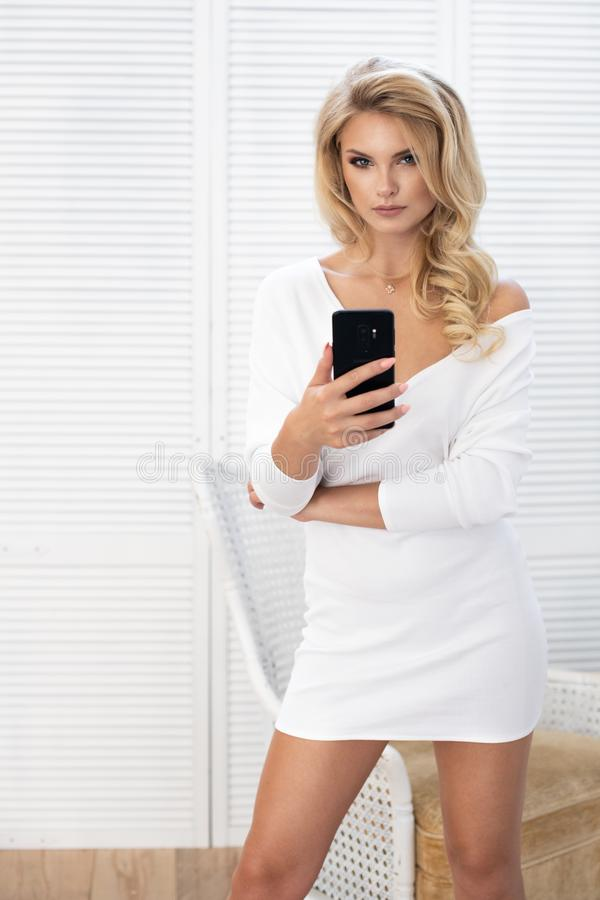 Attractive fashion model wears a white dress in studio and smiling. Summer look royalty free stock photos