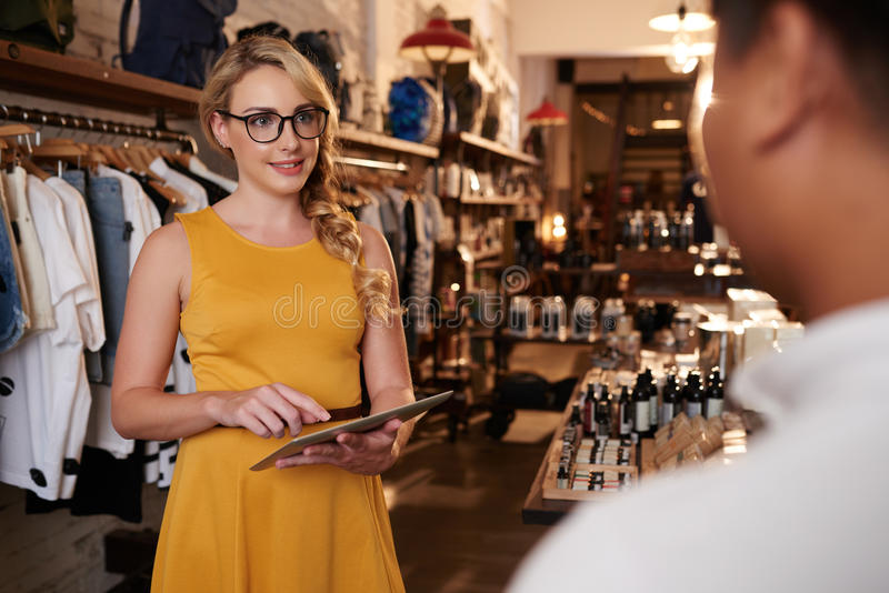 Talking to client. Attractive young female boutique owner talking to client royalty free stock photography