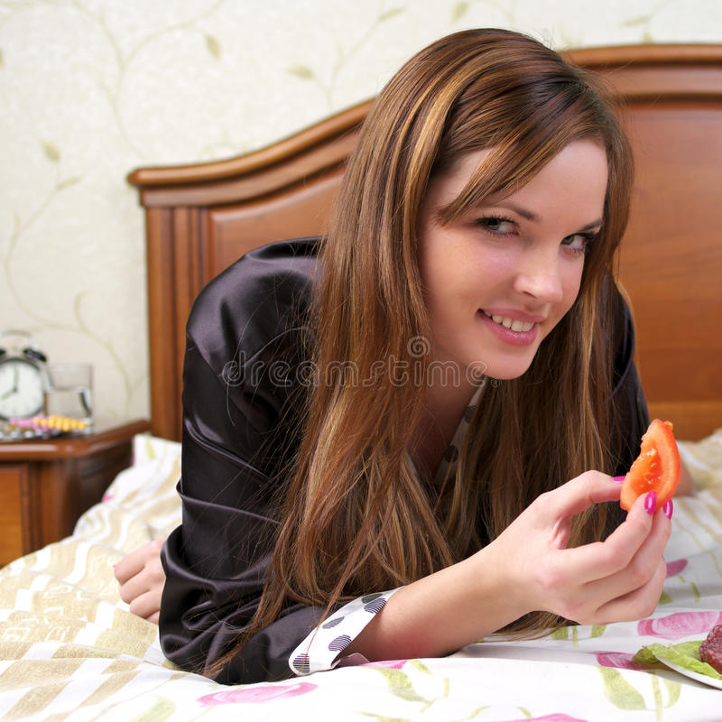 Attractive young female eating royalty free stock photography