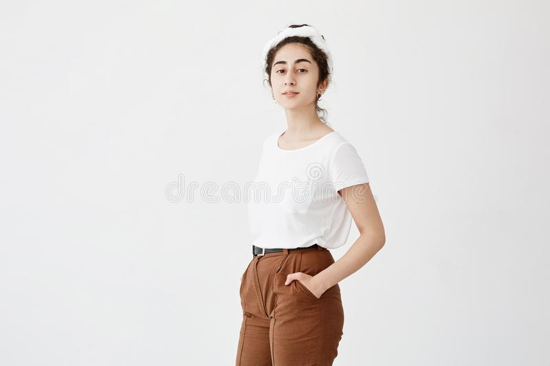 Attractive young female model with dark and wavy hair in bun, wearing white t-shirt and trousers, keeping her hands in stock image