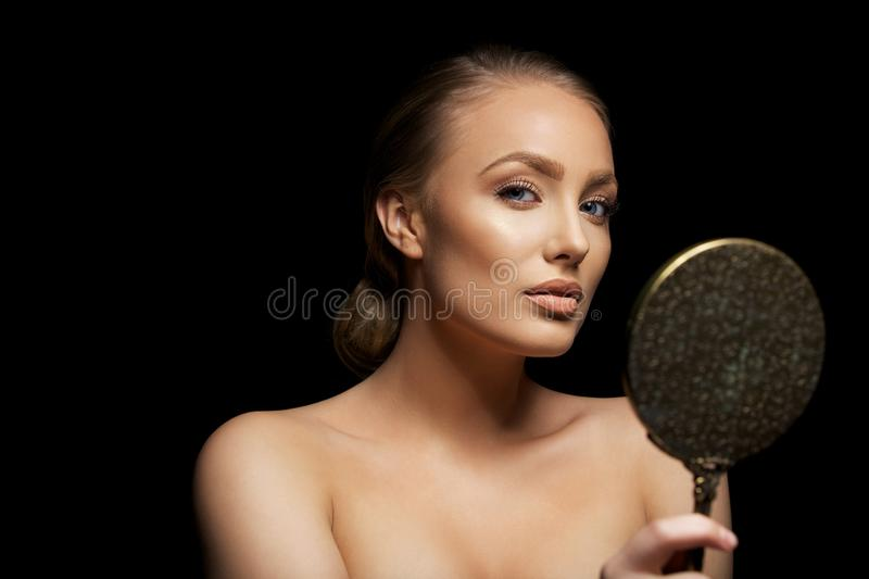 Attractive young female model with a mirror. Portrait of attractive young female model holding a hand mirror looking at camera. young woman against black royalty free stock images