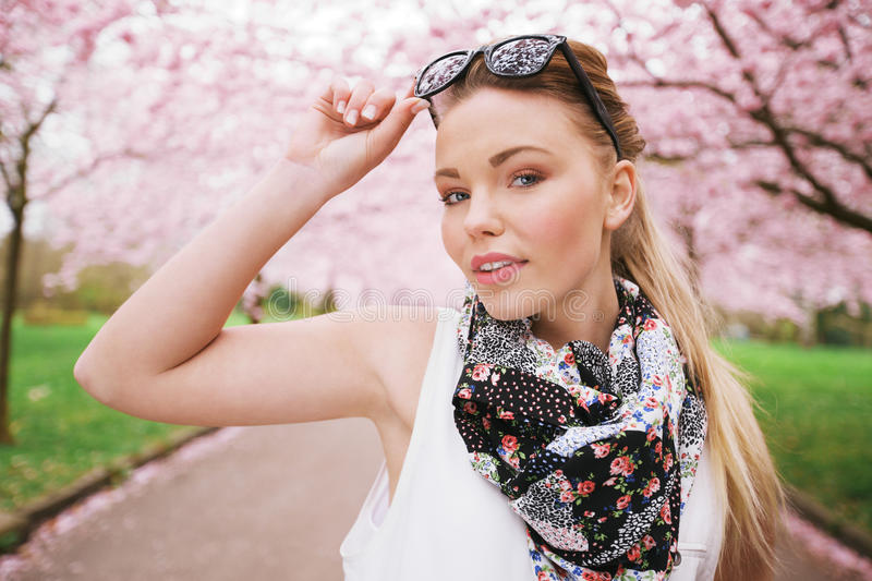 Attractive young female model posing at spring park. Casual young woman wearing sunglasses and scarf looking at camera royalty free stock images