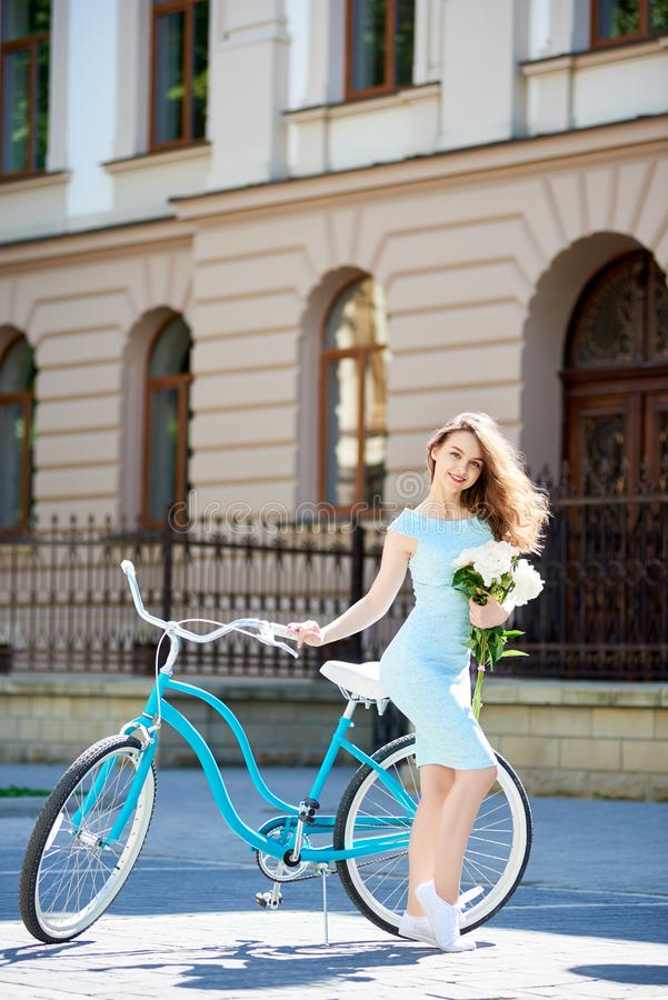 Attractive young female posing with peonies near blue vintage bike in front of historical buiding in city center royalty free stock photo