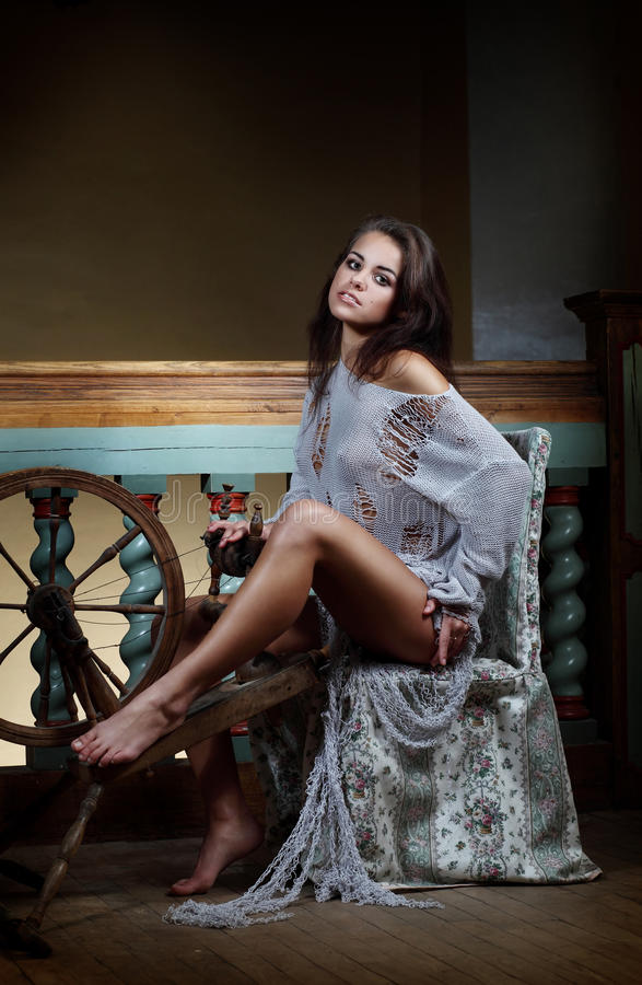Attractive young female is sitting with a distaff for making yarn download attractive young female is sitting with a distaff for making yarn stock photo image sciox Gallery