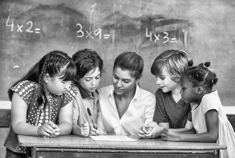 Attractive young female teacher checking multi race classroom work with other students at the desk royalty free stock image