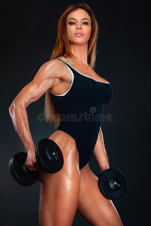 Young fitness woman athlete and bodybuilder with dumbell. Individual sports. Sports recreation. Attractive young fitness woman holding dumbell. Studio shot stock image
