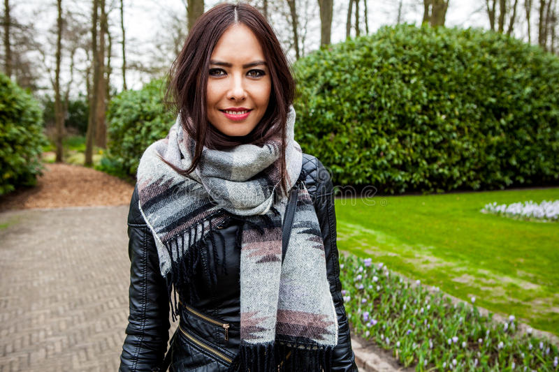 Attractive young friendly woman with long beautiful hairs posing in park.  stock photos