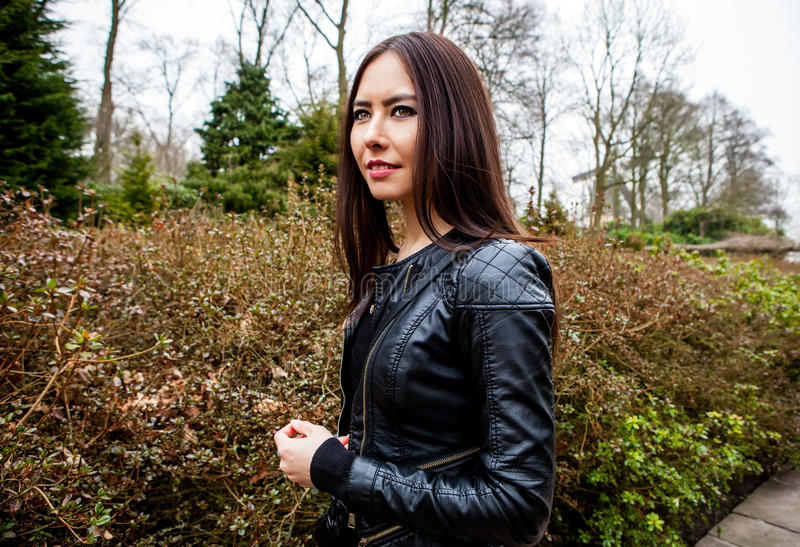 Attractive young friendly woman with long beautiful hairs posing in park.  royalty free stock photos