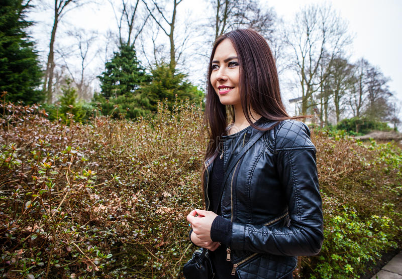 Attractive young friendly woman with long beautiful hairs posing in park.  stock photography