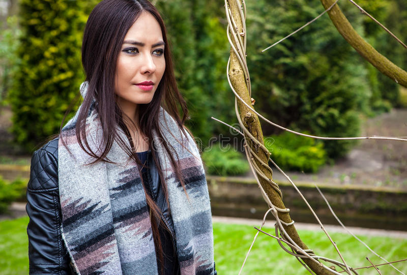 Attractive young friendly woman with long beautiful hairs posing in park.  royalty free stock photo