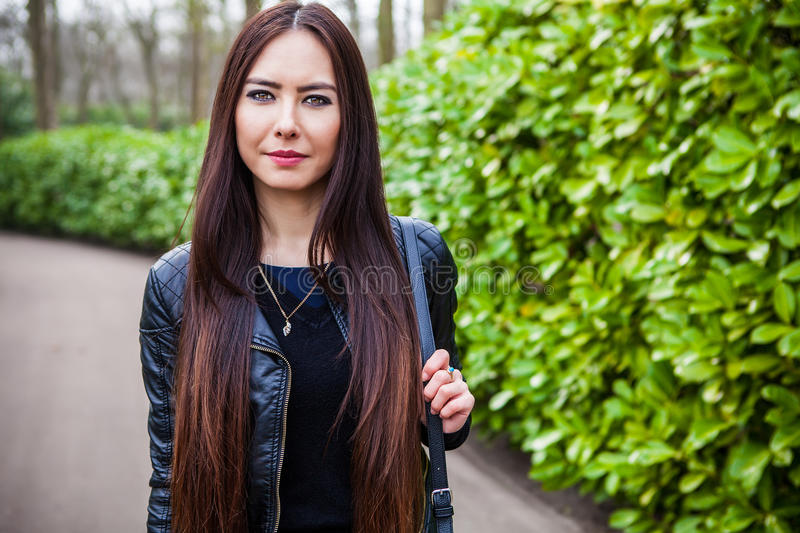 Attractive young friendly woman with long beautiful hairs posing in park.  stock images