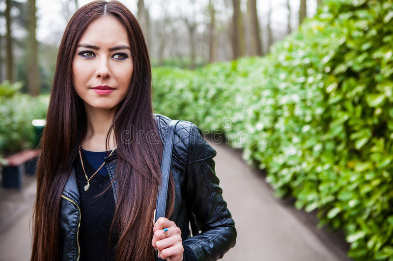 Attractive young friendly woman with long beautiful hairs posing in park.  royalty free stock photography
