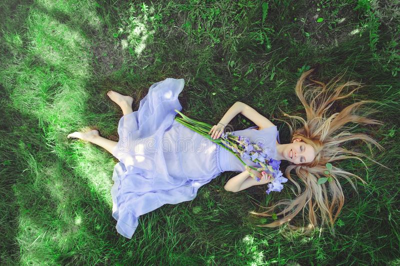 Attractive young girl with blonde hair and natural make-up smelling blue purple iris flowers lying on grass outdoors, tendern stock image