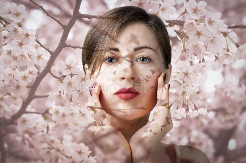 Attractive young girl with blue eyes on background of pink sakura flowers, natural cosmetics concept stock photo