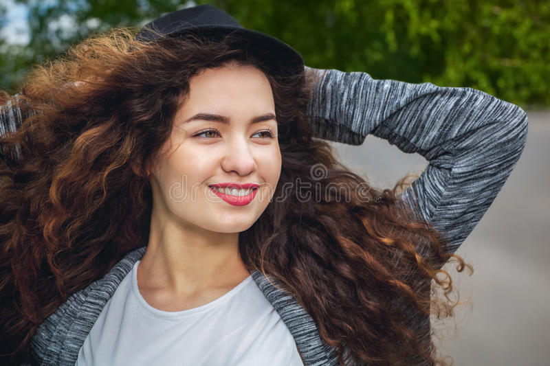 Attractive, young girl with curly hair and a hat on a background of green trees on the lawn royalty free stock photography