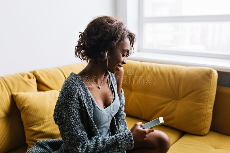 Attractive young girl with curly hair listening music in earphones, with phone in hand, sitting on yellow sofa with royalty free stock images