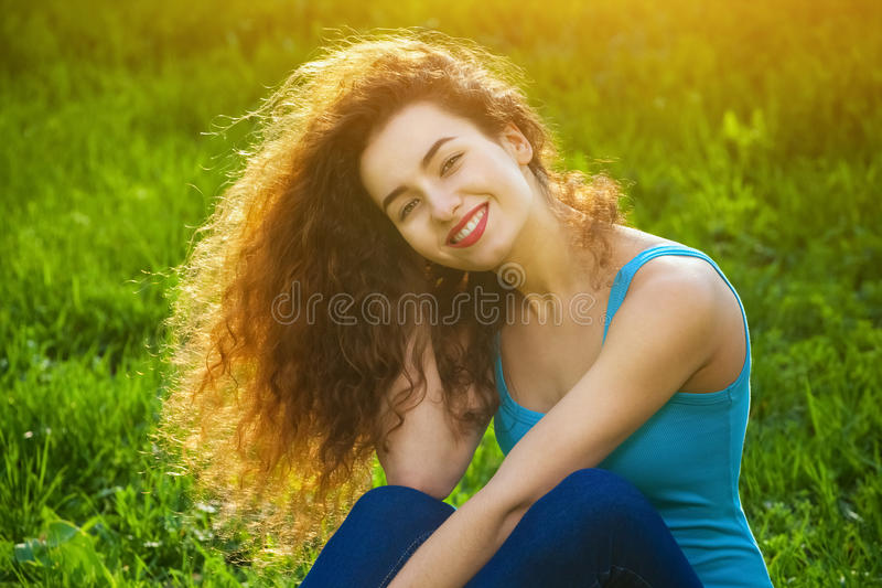 Attractive, young girl with curly hair sitting on the green grass on the lawn and smiling at the photographer. stock photos