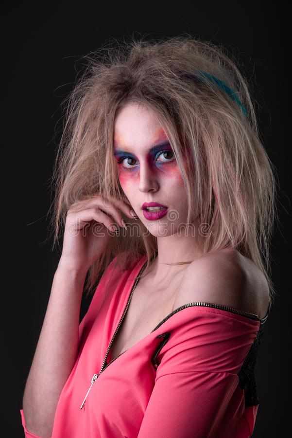 Attractive young girl with disheveled hair. Emotional Portrait of a Attractive young girl with carnival colorful makeup and disheveled hair royalty free stock image
