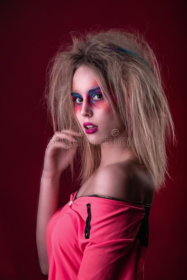 Attractive young girl with disheveled hair. Emotional Portrait of a Attractive young girl with carnival colorful makeup and disheveled hair royalty free stock images