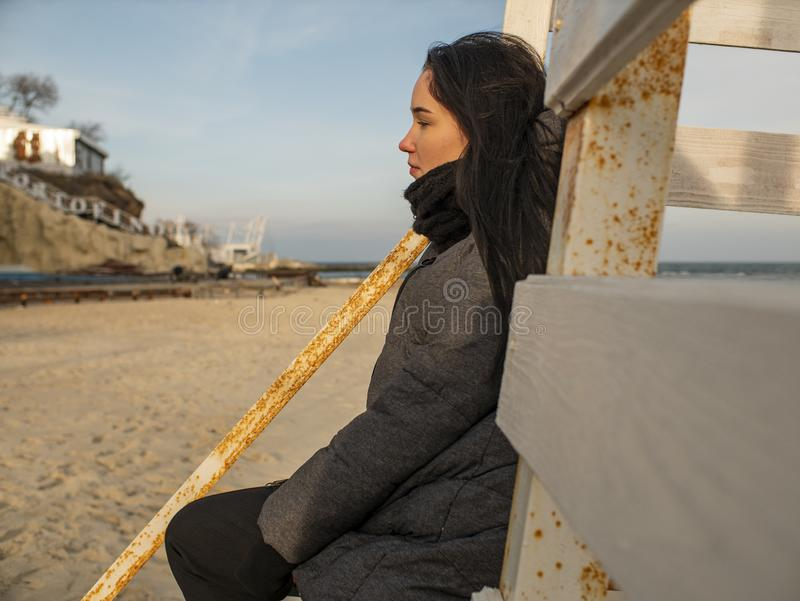 Attractive young girl with disheveled hair sits on a wooden design on the beach in a coat.  royalty free stock image