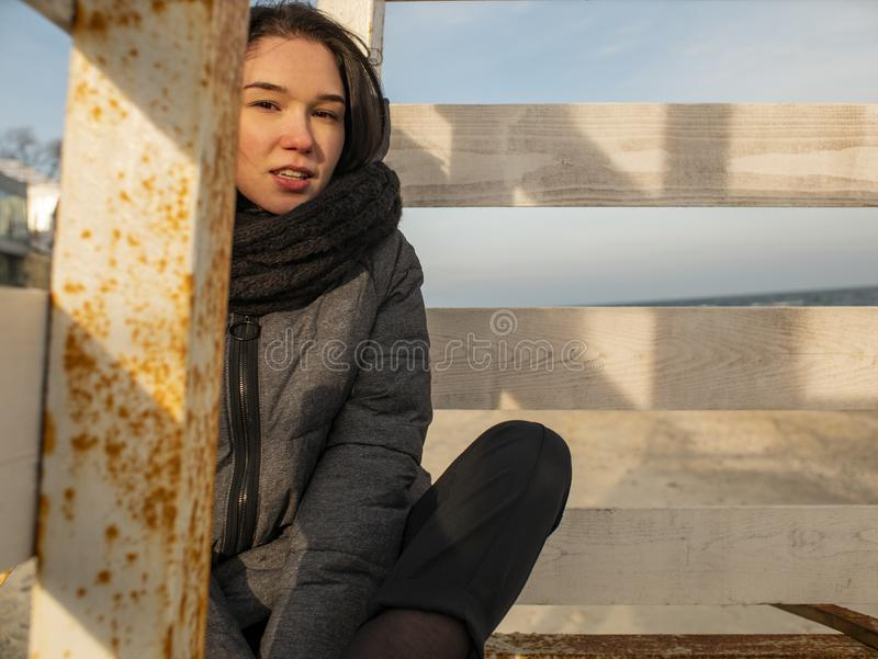 Attractive young girl with disheveled hair sits on a wooden design on the beach in a coat.  royalty free stock photos