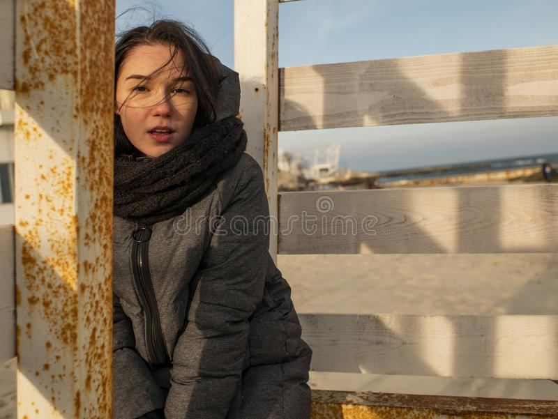 Attractive young girl with disheveled hair sits on a wooden design on the beach in a coat stock photo
