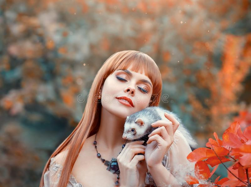 Attractive young girl with fiery red straight hair plays with her pet, elf princess plays animal fairy with wild ferret. Holds it in her hands on her shoulder royalty free stock image
