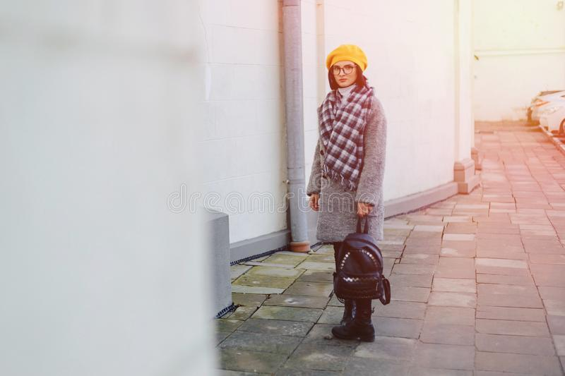 Attractive young girl in glasses in coat and yellow Beret freestyle walking stock photography