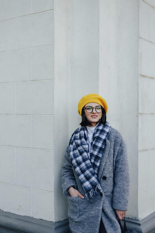 Attractive young girl in glasses in coat and yellow Beret on a simple light background royalty free stock photos