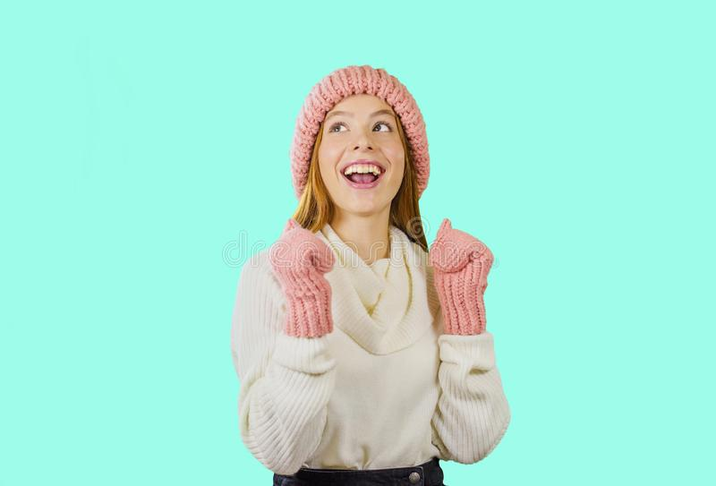 Attractive and young girl in a hat and mittens with a smile looks upwards on an isolated background stock photo