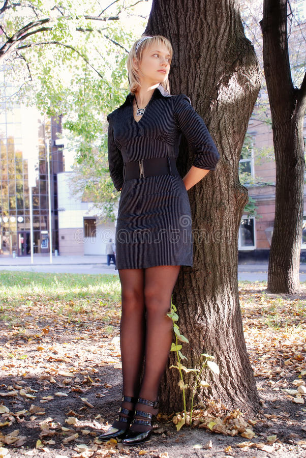 Attractive young girl hiding behind the tree stock photography