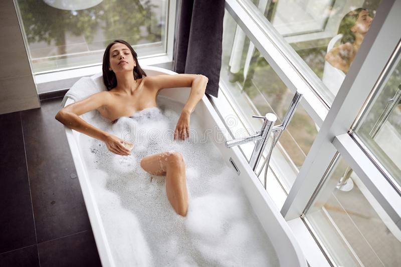 Attractive girl relaxing in bath with foam and drink champagne top view stock photography