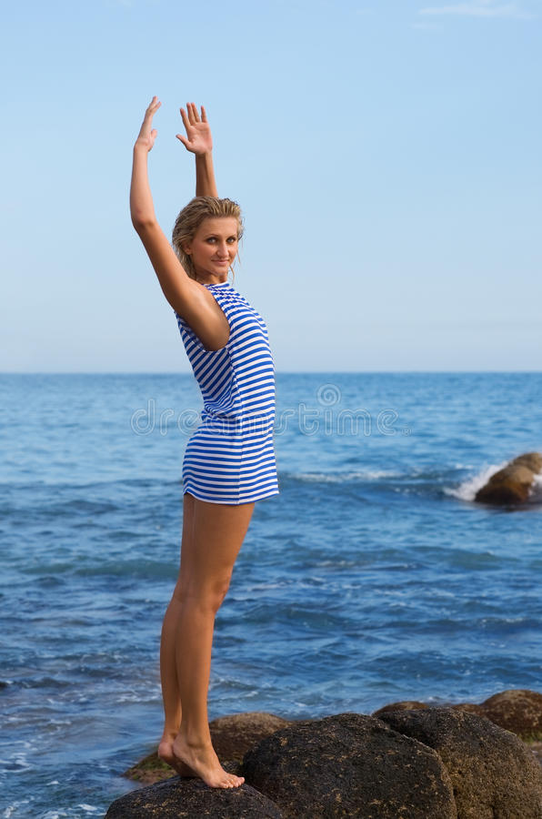 Attractive young girl on a rocky seashore. Evening royalty free stock image