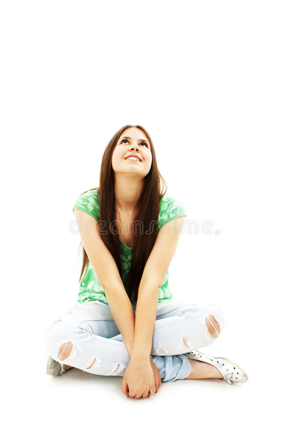 Attractive young girl sitting on the floor looking royalty free stock photo