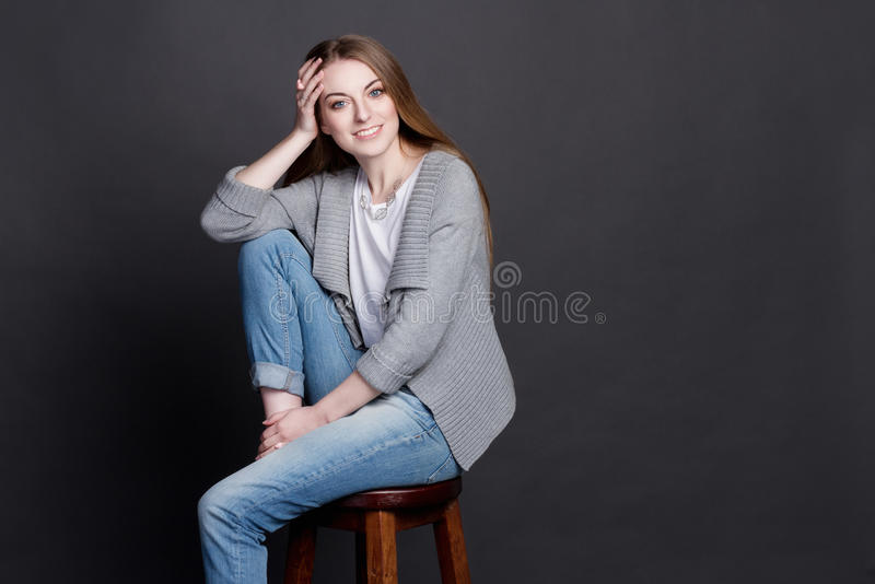 Attractive young girl sitting on high wooden chair. She smiles sincerely. royalty free stock photography