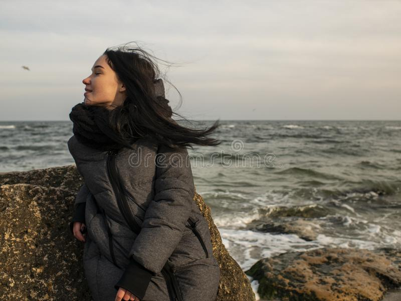 Attractive young girl sitting on a stone near the sea on a background of gray sky royalty free stock photography