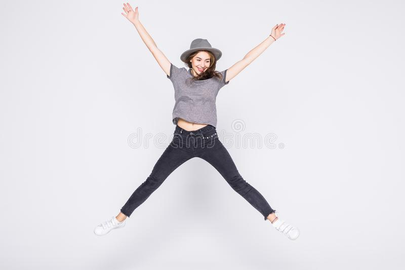 Attractive beautiful young girl wearing casual flying in air isolated over grey background stock image