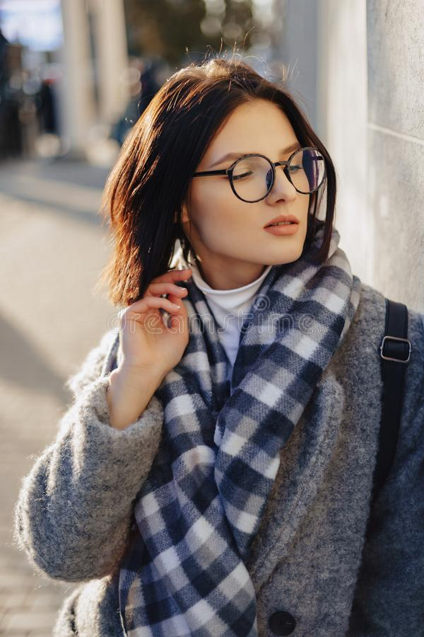 Attractive young girl wearing glasses in a coat walking on a sunny day royalty free stock images