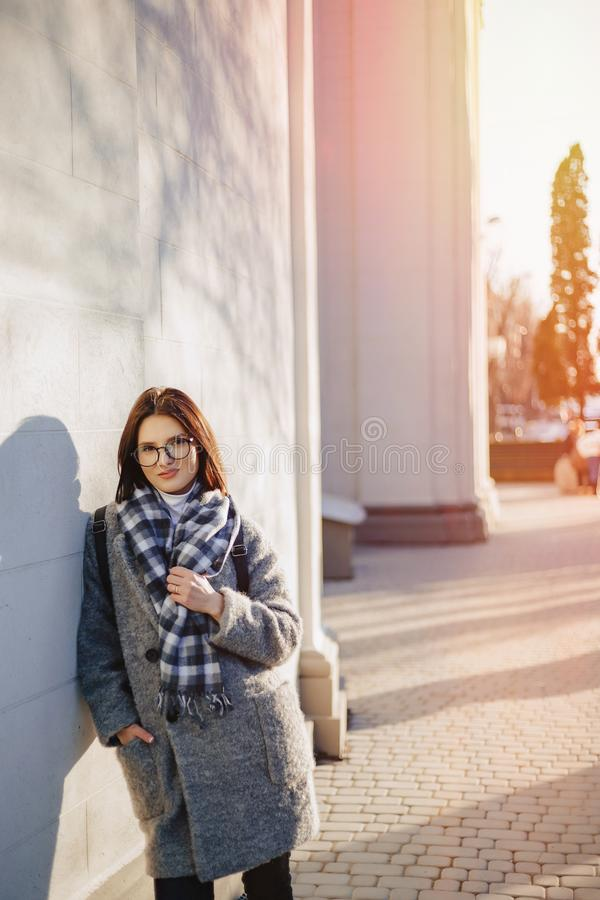 Attractive young girl wearing glasses in a coat walking on a sunny day royalty free stock photos