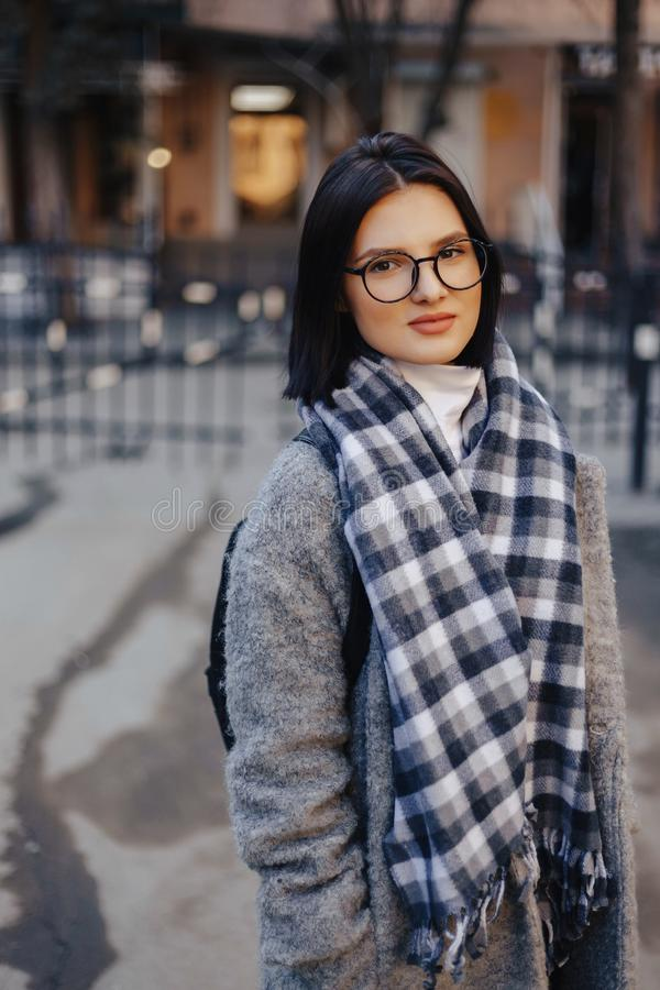 Attractive young girl wearing glasses in a coat walking on a sunny day royalty free stock photography