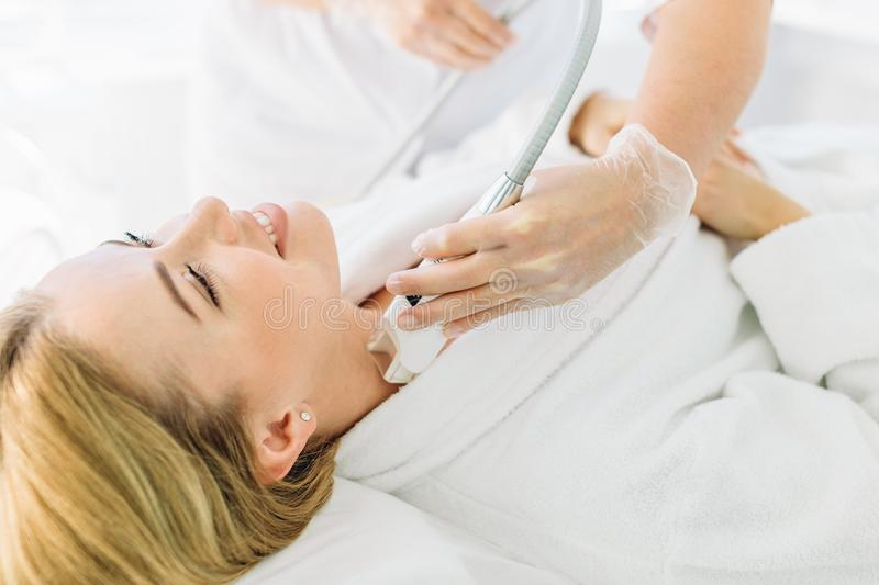 Blonde woman with long hair makes face laser resurfacing At Beauty Center. Attractive young groomed woman pampers herrself with a facial or a body treatment in a stock photography