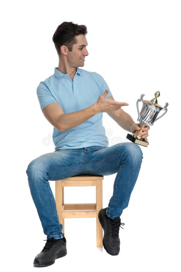 Attractive young guy presenting his trophy royalty free stock photography