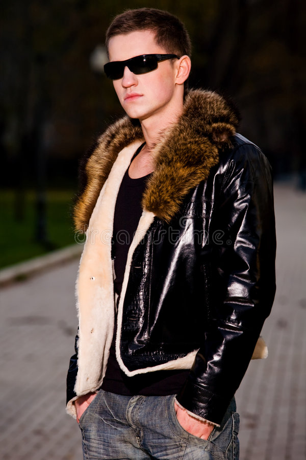 Attractive young guy in winter leather jacket stock images