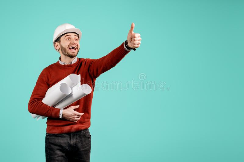 Attractive young handsome bearded engineer or constructor man in casual outfit show ok gesture over cyan background stock images