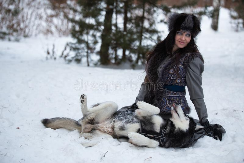Attractive young happy woman sitting and playing with husky dog. Attractive young woman sitting and playing with husky dog over snow park background royalty free stock images
