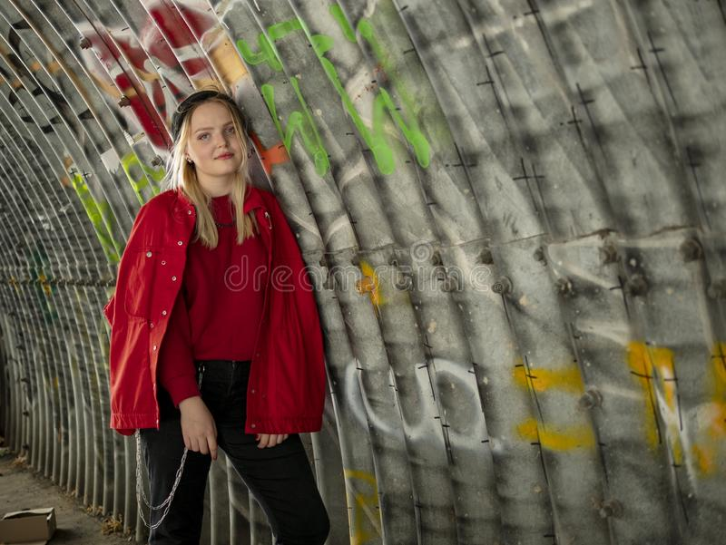 Attractive young hipster girl in knitted hat and red jacket is standing under a bridge against the background of a wall with stock image