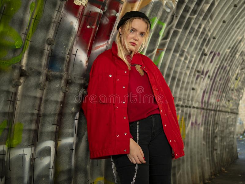 Attractive young hipster girl in knitted hat and red jacket is standing under a bridge against the background of a wall with royalty free stock images