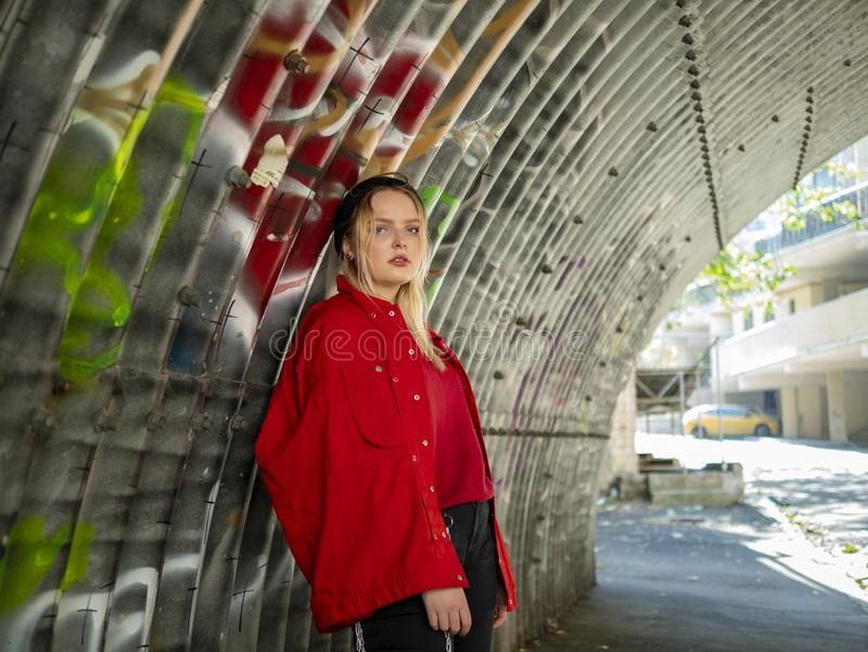 Attractive young hipster girl in knitted hat and red jacket is standing under a bridge against the background of a wall with royalty free stock image
