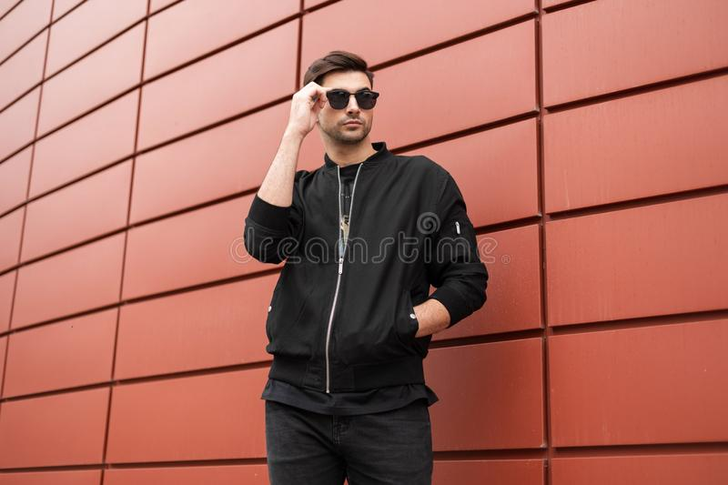 Attractive young hipster man in fashionable black clothes straightens trendy sunglasses. Stylish urban model guy stands outdoors. In the city near the red metal royalty free stock photography